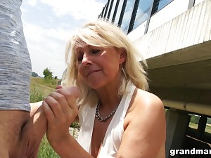 Slutty granny gives a blowjob in public and shows wet white trunks